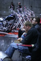 Dining on Custom Harley Row: Booth workers chow down on lunch.  In the background: a row of Harley-Davidson custom bikes.